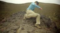 Hiker slowly descends rock bolder video