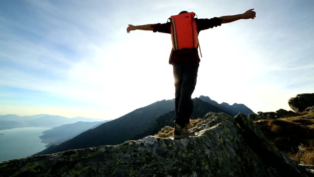 Hiker stands on mountain ridge crest, arms outstretched video
