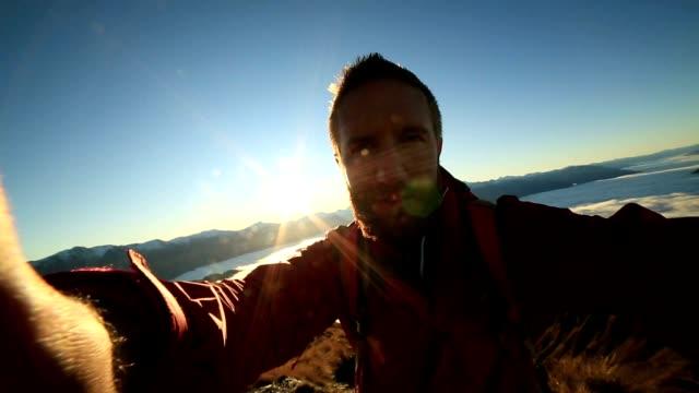 Hiker takes selfie portrait on mountain peak above clouds video
