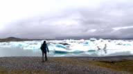 Hiker taking photos at Jokulsarlon glacier lagoon in East Iceland. Static shot. video