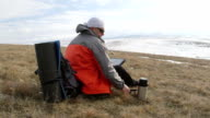 Hiker using tablet computer on the snowy mountain plateau video
