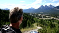 Hiker walks along mountain ridge above valley video