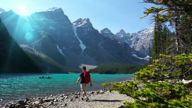 Hiker walks toward lake in the mountians video