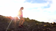 Hiker with Backpack Hiking on top of a mountain with sun flares. Young Healthy Woman Adventure in Nature. video