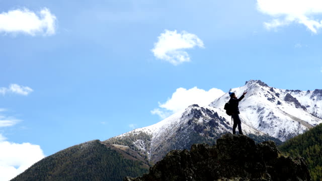 Hiker with backpack standing on top of a mountain with raised hands and enjoying sunrise video