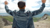 Hiker with backpack standing on top of a mountain with raised hands and enjoying sunrise. video