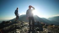 Hikers celebrating on mountain peak, slow motion video
