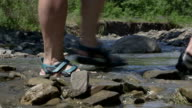 Hikers crossing mountain creek by the ford video