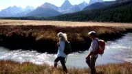 Hikers follow shoreline of mountain creek video