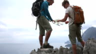 Hikers look at map on ridge crest above sea, mountains video