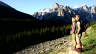 Hiking couple ascend mountain slope, man provides assistance video