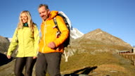 Hiking couple descend slope below Matterhorn video