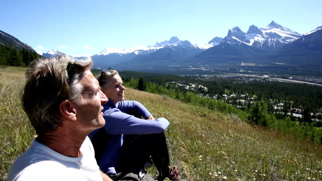 Hiking couple look off from mountain slope to distant view video