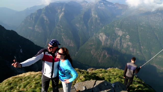 Hiking couple take pictures from mountain summit, besides others video