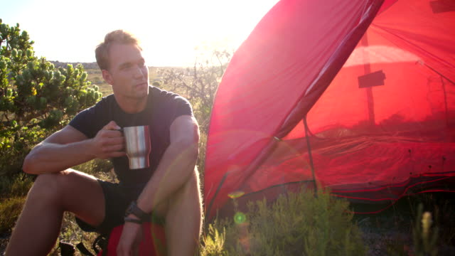 Hiking man drinking coffee next to camping tent in nature video