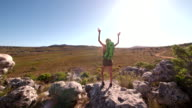 Hiking woman cheering on top of mountain in nature video