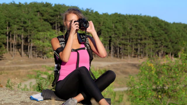 Hiking young woman taking pictures during hike trekking video