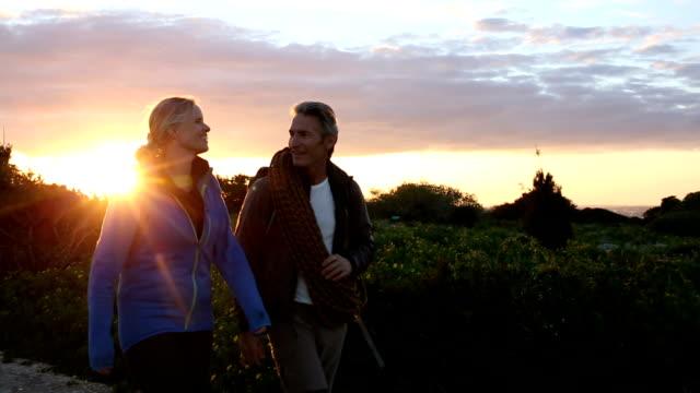 Hiking/climbing couple walk along path at sunrise video