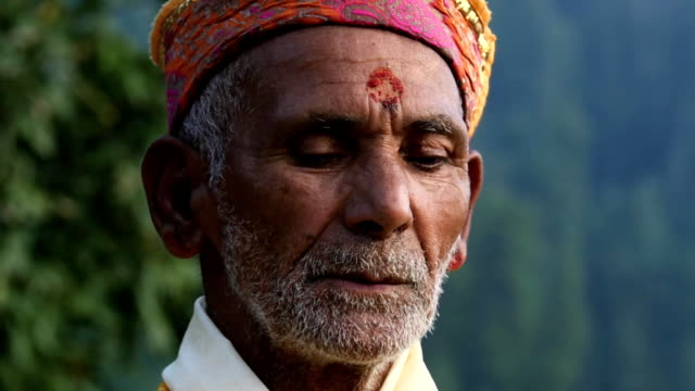 A Hindu old man in yellow offering special spiritual prayer to god video
