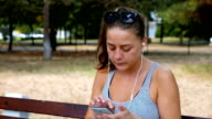 Hip teenager sitting on a bench in the park and listening to music played from her smart phone video