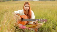 Hippie girl playing guitar on grass video