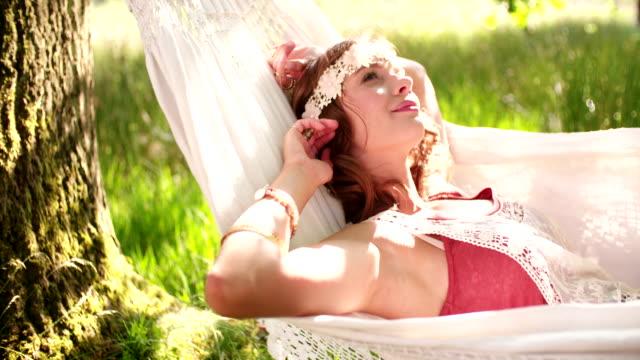 Hippie girl relaxing in a hammock in a sunlit park video