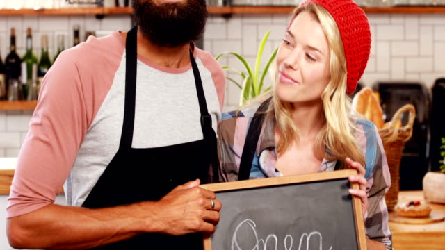 Hipster couple holding open sign video
