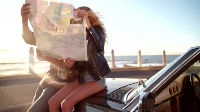 Hipster couple planning their summer seaside road trip with convertible video