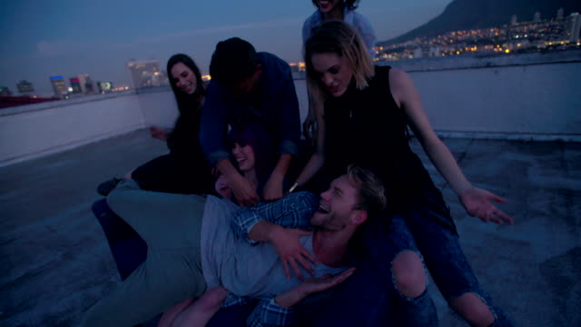 Hipster friends dancing and talking on a rooftop party video
