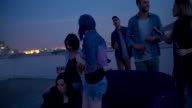 Hipster friends drinking and talking on a rooftop party video