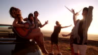Hipster friends enjoying road trip with a guitar during sunset video