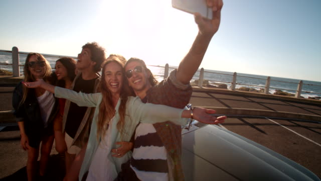 Hipster friends grimacing taking a selfie at the beach video