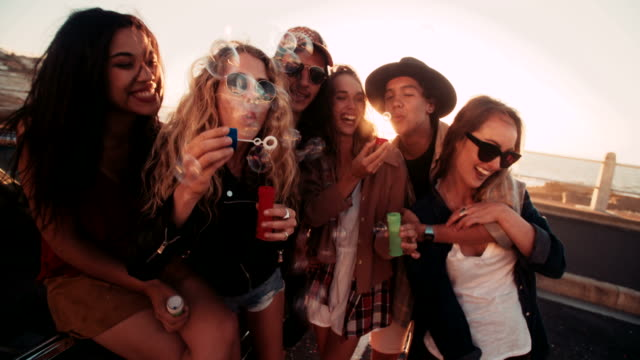 Hipster friends having bubbles party outdoors video