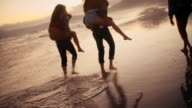 Hipster friends having funny piggyback rides on beach at sunset video