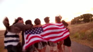 Hipster friends running on country road holding an American flag video