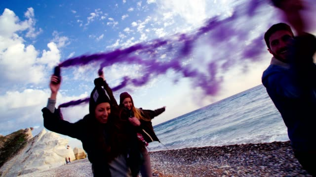 Hipster friends running with smoke bombs on a beach video