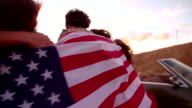 Hipster friends walking on country road holding an American flag video