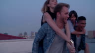 Hipster fun loving friends doing piggyback rides on rooftop video