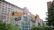 Hipster girl holding longboard video