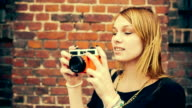 Hipster girl taking photos with vintage camera video