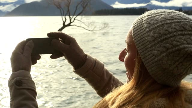 Hipster girl traveling takes picture of landscape using mobile phone video