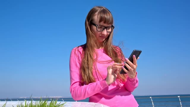 Hipster girl writing sms on her smartphone video