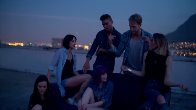 Hipster girls partying around a couch on a rooftop video