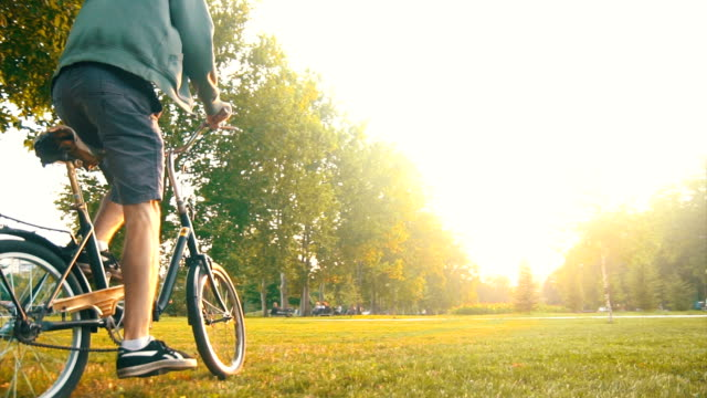 Hipster guy riding his bicycle on the grass video