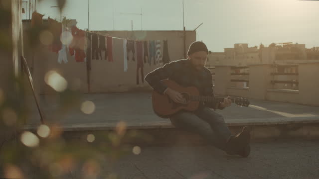 Hipster man playing acoustic guitar on the terrace video