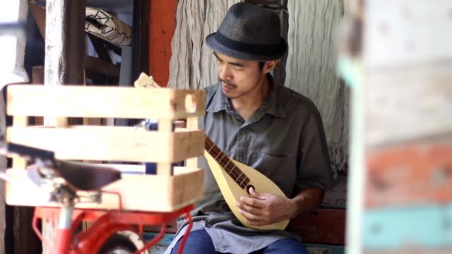 hipster man playing local mandolin video