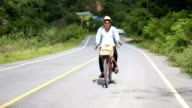 Hipster man ride vintage bicycle traveling on the countryside video