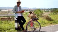 Hipster man traveling from the old travel books with vintage bicycle video