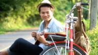 Hipster man traveling with vintage bicycle and playing ukulele video