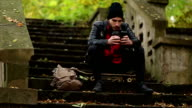 Hipster sitting on stairs and using phone video